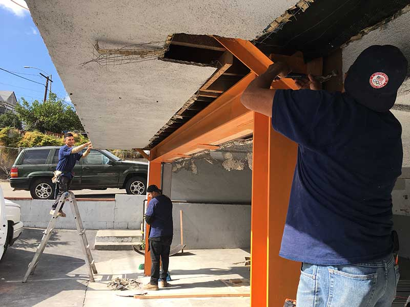 Three American Retrofitter employee's installing a new moment frame, adding lathing, and cleaning up at a soft-story seismic retrofit project in Los Angeles.