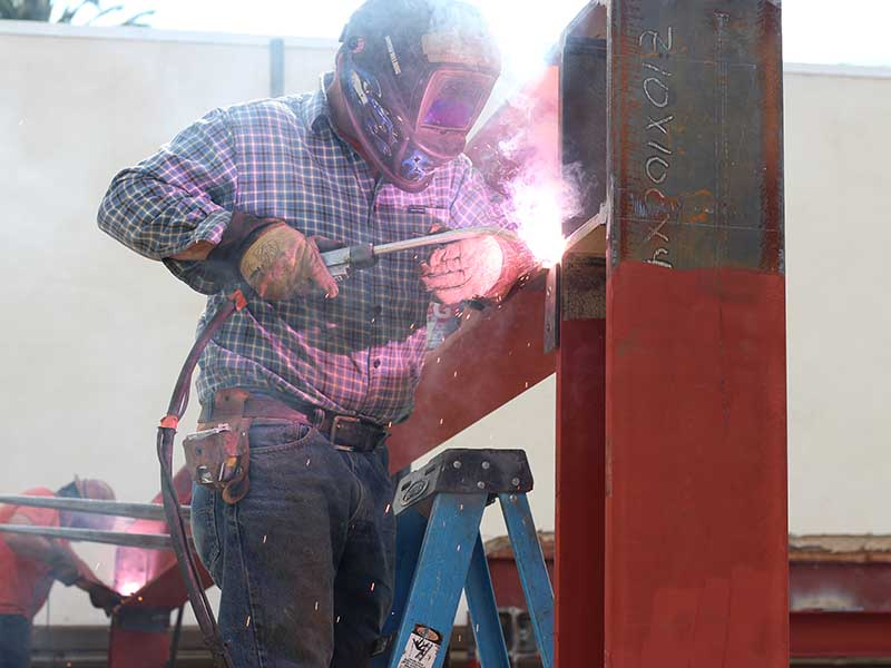 An American Retrofitters employee welding a moment connection to create a moment frame on a soft-story seismic retrofit project in Los Angeles.
